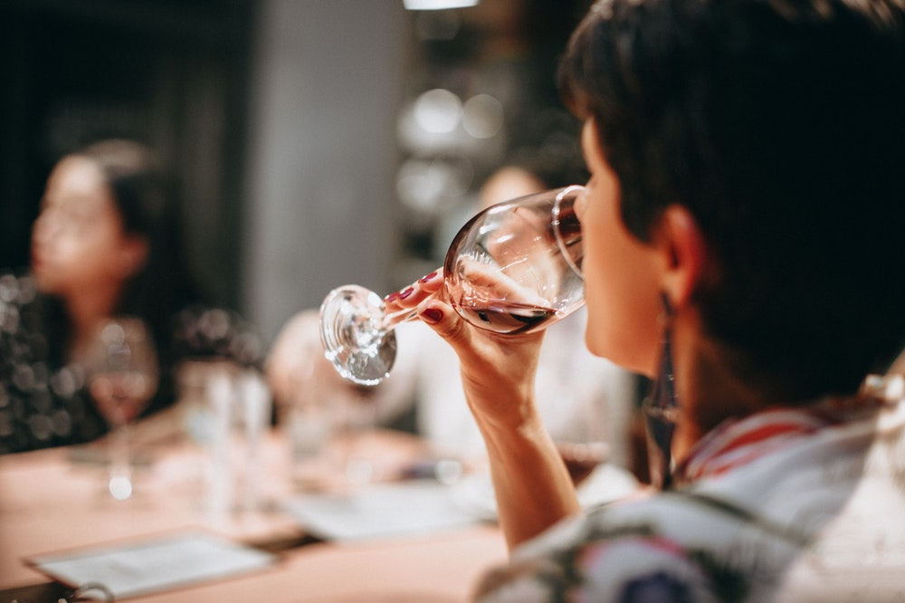 woman wine tasting at home at a dinner table